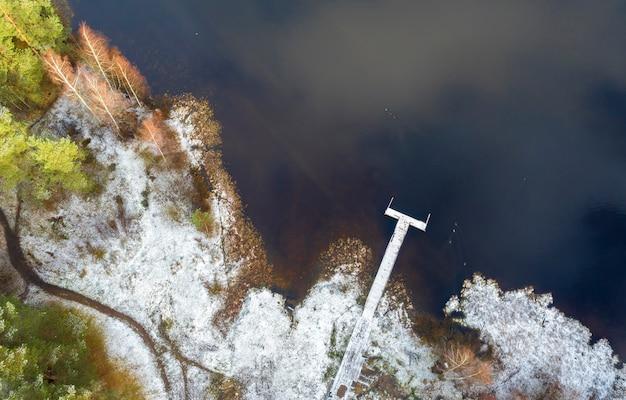 Pier op een bosmeer in de sneeuw in de buurt van het parcours in de vroege winter, luchtfoto