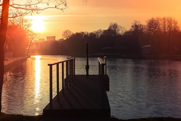 Pier op het meer in het stadspark herfstzonsondergang een prachtig zonnepad op het water
