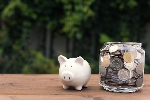 Piggy bank en geld munten glazen pot op houten tafel met de natuur