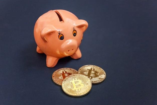 Piggy bank en gouden bitcoin munt virtueel geld op zwarte tafel