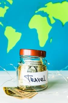 Piggy bank voor reizen met dollars en garland op een achtergrond van een heldere wereldkaart. geld voor reizen. accumulatieconcept