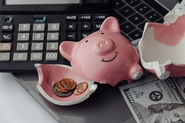 Piggy, rekenmachine en dollarbiljetten op laptop gebroken. financiën en faillissementsconcept