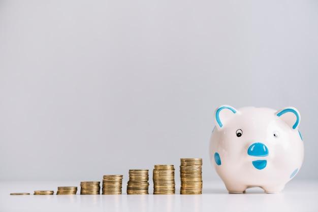 Piggybank en toenemende gestapelde munten op reflecterend bureau