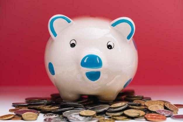 Piggybank over munten voor rode achtergrond