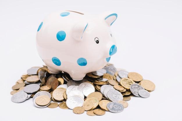 Piggybank over vele munten op witte achtergrond