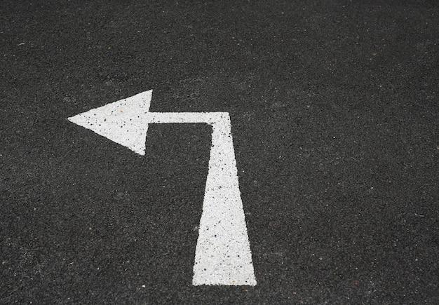 Pijl draai links markerend teken op nieuwe asfaltweg.