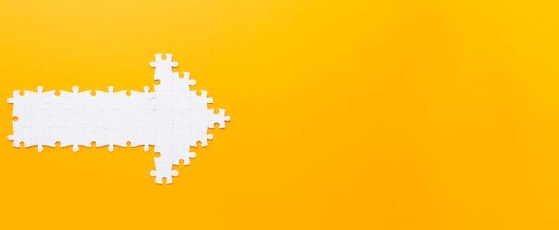 Pijl gemaakt met puzzelstukjes naar rechts wijzend