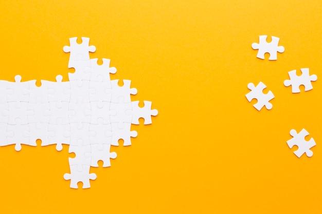 Pijl gemaakt van puzzelstukjes die naar andere stukjes wijzen