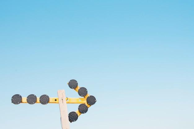 Pijl met cirkelvormige lichten op een houten stok