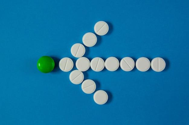 Pijl van pillen geeft van bovenaf een groene pil op een blauwe achtergrond aan