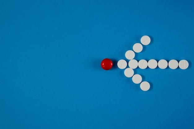Pijl van pillen geeft van bovenaf een rode pil op blauwe tafel aan