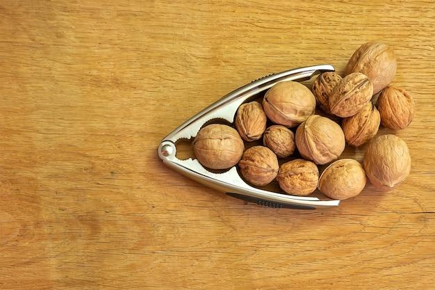 Pijl van walnoten en notenkraker op een houten ondergrond.