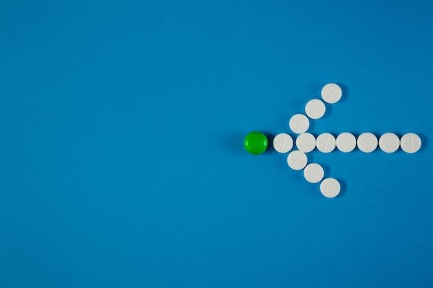 Pijl van witte pillen geeft groene pil aan