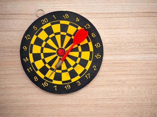 Pijltjepijl en dartboard op bruine houten achtergrond