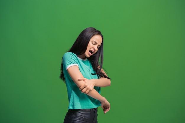 Pijn concept. mooi vrouwelijk portret dat op groene achtergrond wordt geïsoleerd. jonge emotionele verrast vrouw camera kijken. menselijke emoties, gezichtsuitdrukking concept.