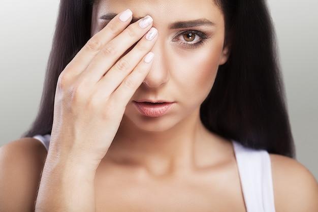 Pijn. depressief overgewicht is een mooie jonge vrouw met zwart haar die lijdt aan ernstige hoofdpijn en een ontroerend hoofd.