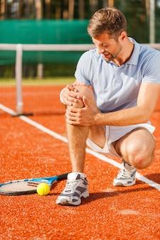 Pijn in de knie voelen. close-up van een tennisser die zijn knie aanraakt en grimassen trekt terwijl hij op de tennisbaan zit