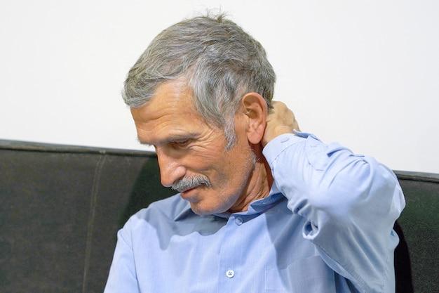 Pijn in de nek van man door vermoeidheid. oude man masseert haar pijnlijke nek met haar handen.