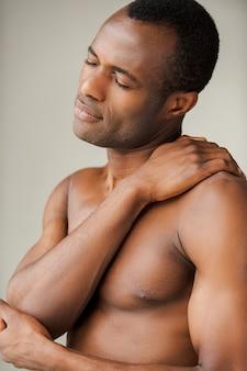 Pijn in de schouder voelen. jonge gespierde afrikaanse man die zijn schouder aanraakt terwijl hij tegen een grijze achtergrond staat