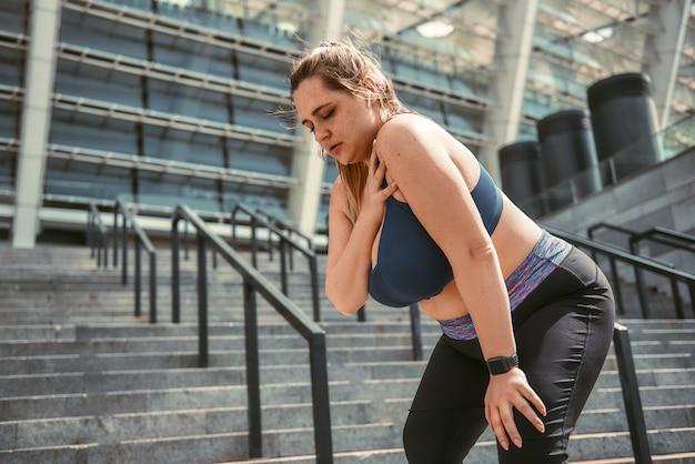 Pijn na training jonge plus size vrouw die haar schouder aanraakt en pijn voelt na het sporten