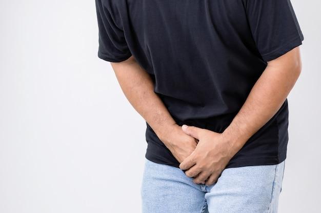 Pijn op penis concept: man gebruikt zijn handen om op zijn penis op een grijze muur te drukken. gebruikt voor prostaatkanker