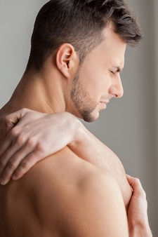 Pijn voelen na het sporten. achteraanzicht van jonge gespierde man die zijn schouder aanraakt en negativiteit uitdrukt terwijl hij geïsoleerd op een grijze achtergrond staat