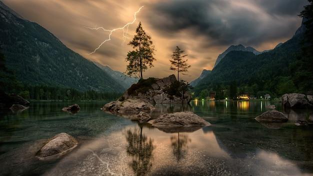 Pijnbomen op rotsformatie in de buurt van bergen onder grijze wolken