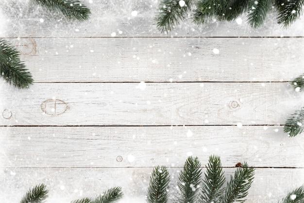 Pijnboombladeren als kader op een witte houten achtergrond met sneeuwvlokken worden verfraaid die. vrolijk kerstfeest en winter vakantie achtergrond.