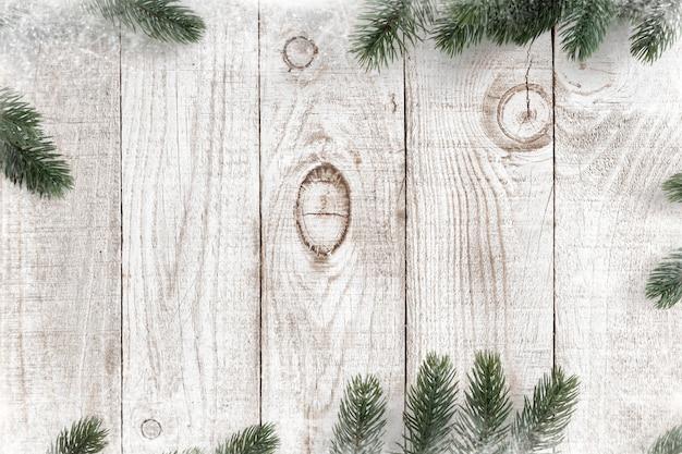 Pijnboombladeren als kader op een witte houten achtergrond met sneeuwvlokken worden verfraaid die