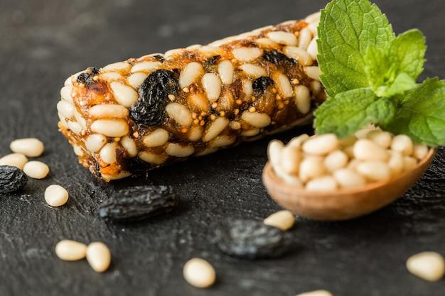 Pijnboompitten energierepen met gedroogd fruit & diverse noten op betonnen muur. gezond veganistisch superfood, verschillende fitnessdieetsnacks voor een sportieve levensstijl.
