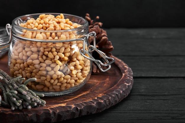 Pijnboompitten in een glazen schaal op een donkere tafel met noten verspreid.
