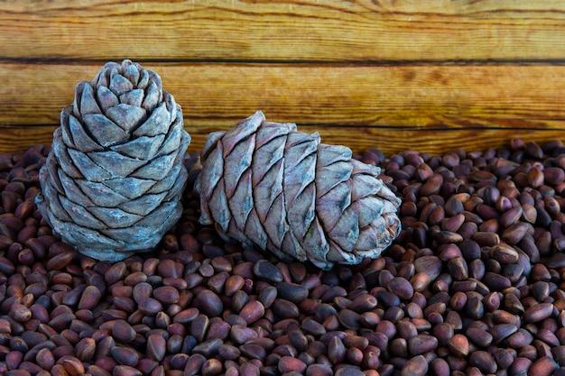 Pijnboompitten. pijnboompitten en kegels op een houten tafel. zaden van siberische den in de schelp. goede voeding