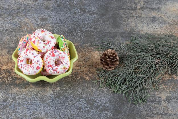 Pijnboomtak en een kegel naast een kleine kom met donuts op marmeren oppervlak
