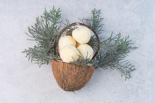 Pijnboomtak, zandkoek en kokosnoot, op het marmer.