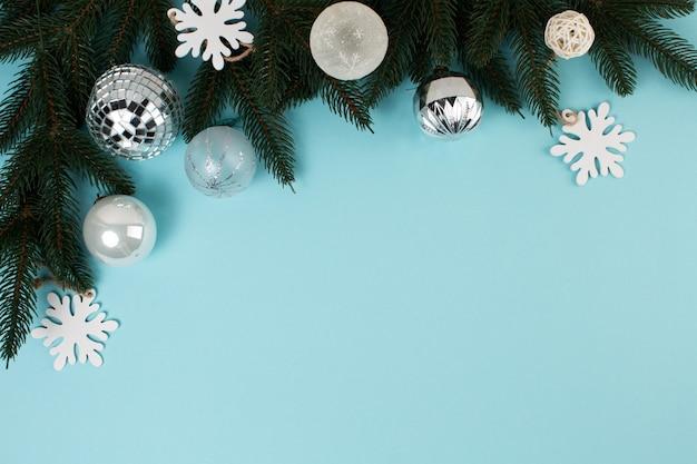 Pijnboomtakken en kerstboomversieringen op een blauwe achtergrond