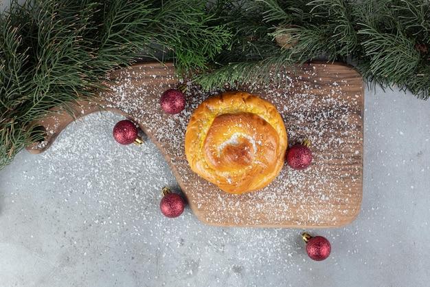 Pijnboomtakken, houten plank, kerstboomspeelgoed en een klein broodje op marmeren oppervlak