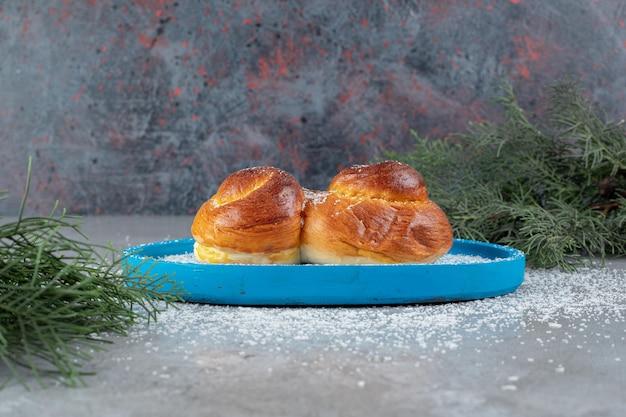 Pijnboomtakken naast een kleine schotel met een zoet broodje op marmeren tafel.