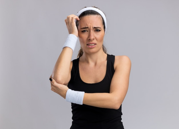 Pijnlijk jong mooi sportief meisje met hoofdband en polsbandjes die de hand op de elleboog houden