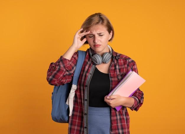 Pijnlijk jong slavisch studentenmeisje met hoofdtelefoons die rugzak dragen die hand op voorhoofd zetten die boek en notitieboekje houden