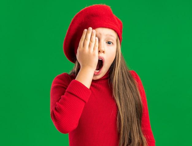 Pijnlijk klein blond meisje met een rode baret die de hand in de gaten houdt met open mond geïsoleerd op een groene muur met kopieerruimte