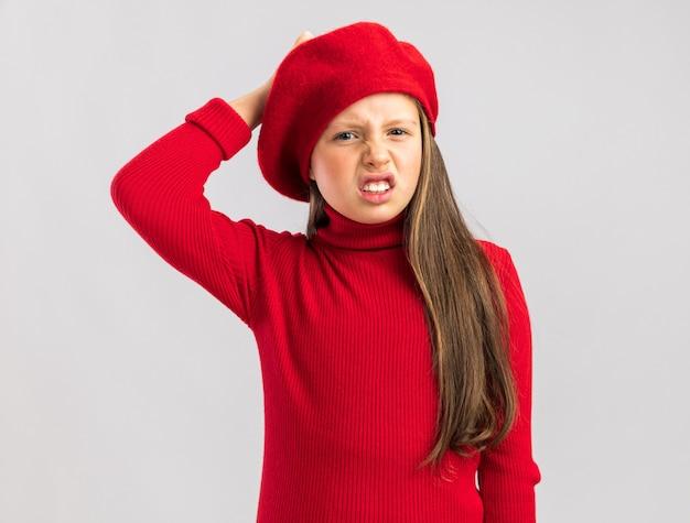 Pijnlijk klein blond meisje met een rode baret die de hand op het hoofd houdt en naar de camera kijkt die op een witte muur met kopieerruimte is geïsoleerd
