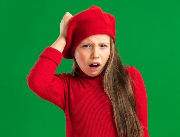 Pijnlijk klein blond meisje met een rode baret die naar de voorkant kijkt en de hand op het hoofd houdt, geïsoleerd op een groene muur