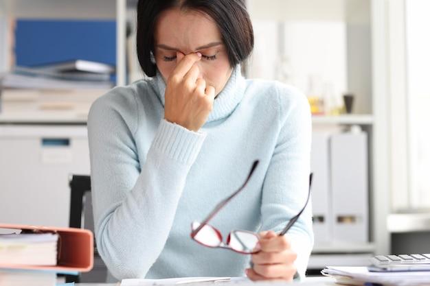 Pijnlijke depressieve vrouw zit met gesloten ogen op de werkplek