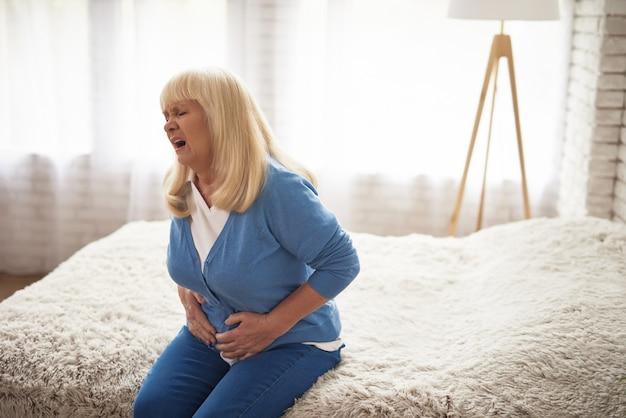 Pijnlijke gezicht van oude vrouw dyspepsie cholesterol.
