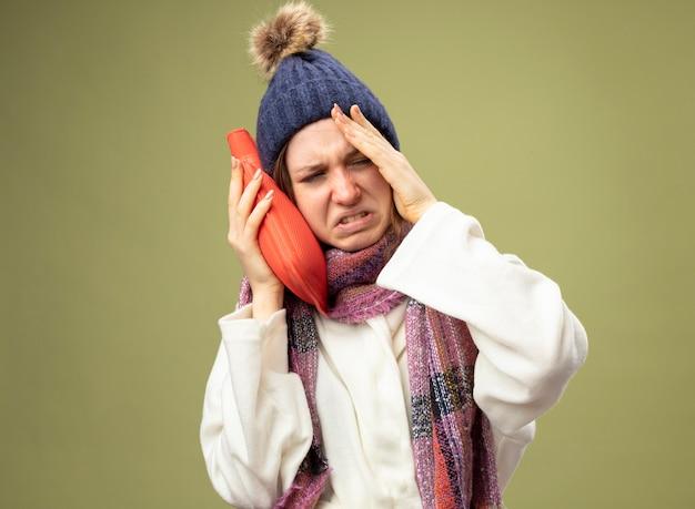 Pijnlijke jong ziek meisje dragen witte mantel en winter hoed met sjaal warm water zak zetten wang hand zetten tempel geïsoleerd op olijfgroen