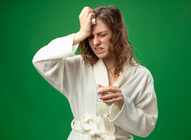 Pijnlijke jong ziek meisje met gesloten ogen dragen wit gewaad glas water houden en hand zetten voorhoofd geïsoleerd op groen