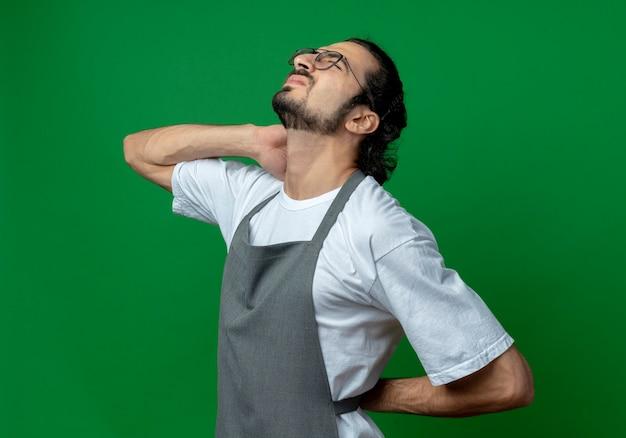 Pijnlijke jonge blanke mannelijke kapper dragen uniform en bril staande in profiel te bekijken handen op nek en rug zetten met gesloten ogen geïsoleerd op groene achtergrond