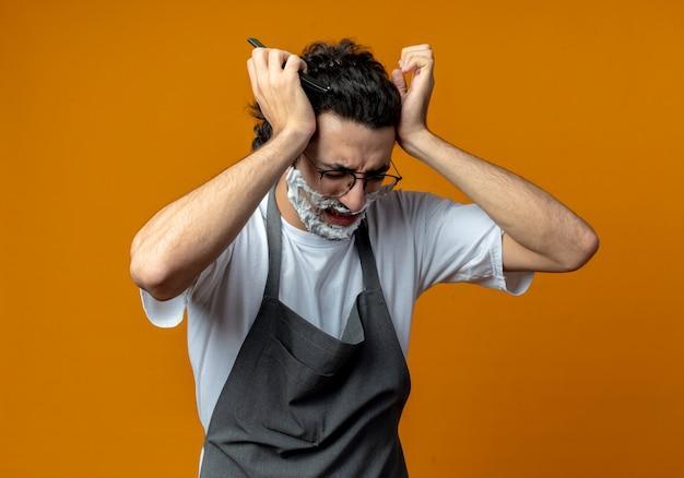 Pijnlijke jonge blanke mannelijke kapper met een bril en een golvende haarband in uniform met een scheermes met scheerschuim op zijn gezicht en met zijn hoofd aan hoofdpijn met gesloten ogen