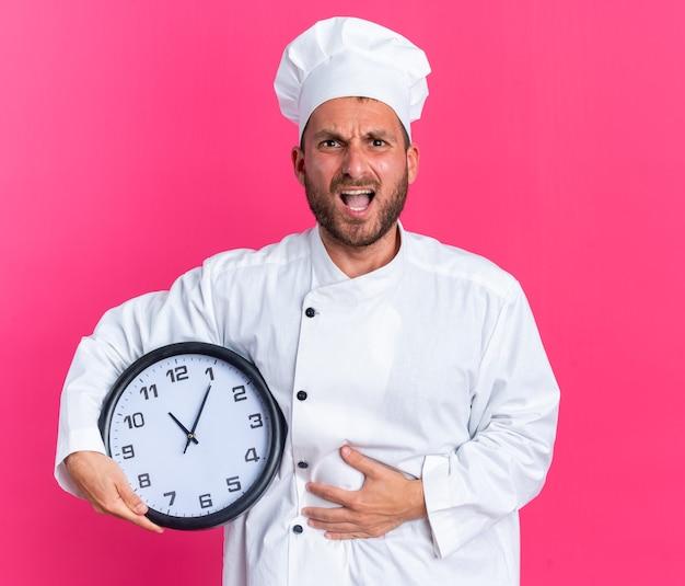 Pijnlijke jonge blanke mannelijke kok in chef-kokuniform en pet met klok die hand op buik houdt