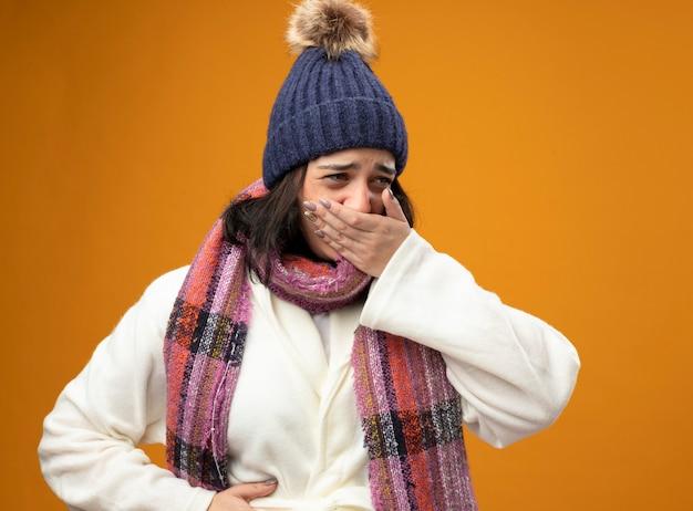 Pijnlijke jonge blanke ziek meisje dragen gewaad winter muts en sjaal met misselijkheid hand op buik en mond te kijken naar kant geïsoleerd op oranje muur